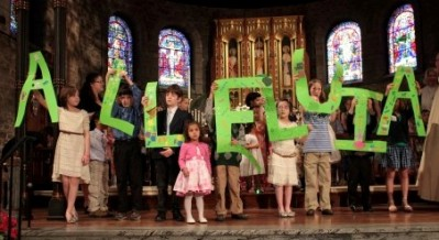 Children hold up letters spelling